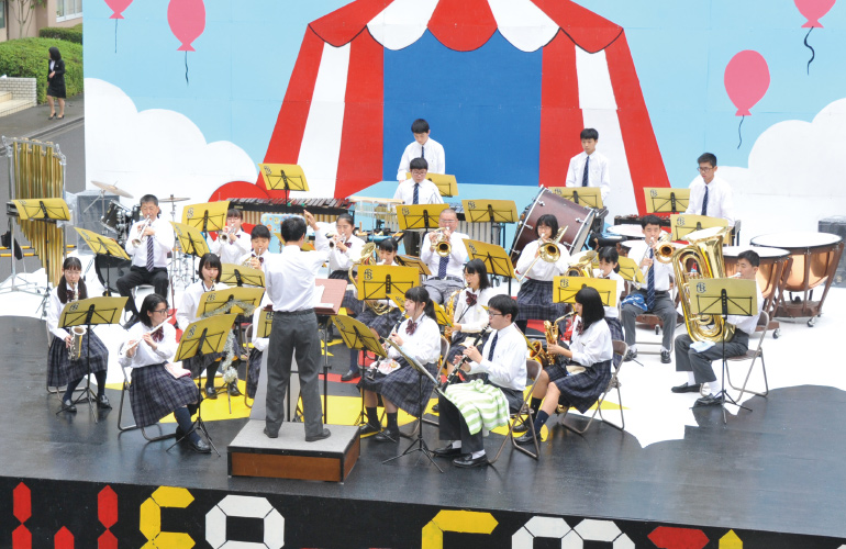 文化発表会(英光祭)の屋外ステージ上で吹奏楽部が演奏している写真です。
