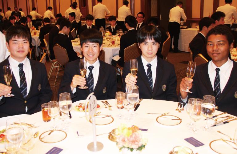 卒業記念昼食会にて、テーブルで乾杯のグラスを持ち上げる男子生徒たちのスナップ写真です。